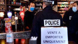 Un policier s'adresse à un restaurateur à Paris, le 6 octobre 2020, lors d'une patrouille visant à inspecter l'application de mesures sanitaires. Photo d'illustration. (THOMAS COEX / AFP)