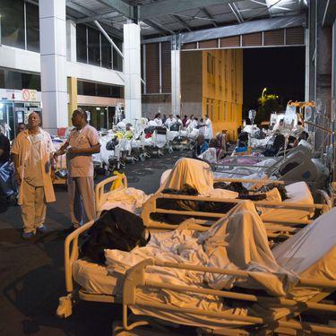 Patients et employés attendent à l'extérieur du CHU de Guadeloupe après son évacuation suite à un incendie, le 28 novembre 2017. (HELENE VALENZUELA / AFP)