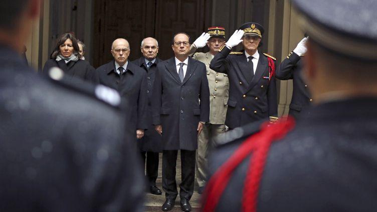 Le président de la République François Hollande (au centre), observe une minute de silence à la préfecture de Paris. A gauche, se trouvent Anne Hidalgo, maire de Paris, et Bernard Cazeneuve, ministre de l'Intérieur. (REMY DE LA MAUVINIERE / AFP)