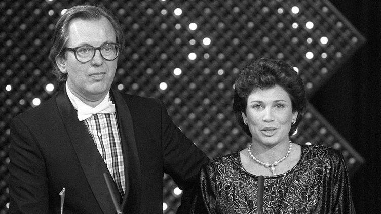 """Jean Lanzi et Anne Sinclair aux 7 d'Or, les défunts Oscars de la télévision où ils avaient été récompensés pour l'hebdomadaire """"7 sur 7"""" (TF1), le 25 octobre 1985 à Paris  (Michel Gangne / AFP)"""