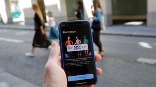 Un homme avec un téléphone dans la main sur lequel est lancé l'application StopCovid, le 27 mai 2020, à Paris. (THOMAS SAMSON / AFP)