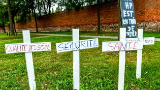"""This photo taken on August 24, 2018 shows Christian crosses installed by caregivers in front of the entrance of the Philippe-Pinel psychiatric hospital in Amiens, reading (L-R) """"Care quality, Security, Health"""" to denounce a serious shortage of nurses and doctors. Employees of the hospital have been striking for the past two months. (PHILIPPE HUGUEN / AFP)"""