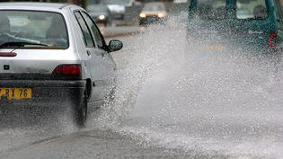 Une voiture roule sous la pluie à Rouen (Seine-Maritime), le 22 juillet 2004. (MAXPPP)