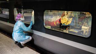 Une soignante observe depuis le quai de la gare d'Austerlitz, à Paris, le transfert par TGV médicalisé d'un patient atteint du Covid-19 vers la Bretagne, où la tension hospitalière est moindre, le 1er avril 2020. (THOMAS SAMSON / AFP)