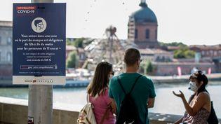 Des passants discutent à Toulouse, près d'un panneau rappelant l'obligaton du port du masque. (FREDERIC SCHEIBER / HANS LUCAS / AFP)