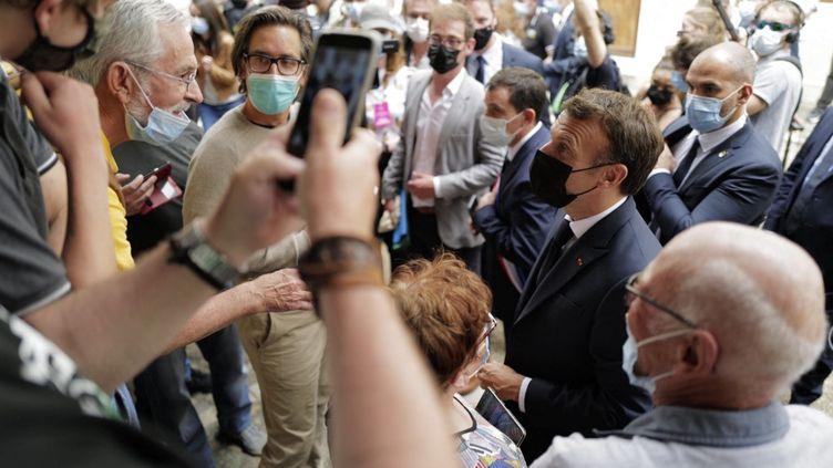 """Emmanuel Macron, que certains présidents de région accusent de faire campagne pour 2022 via son """"Tour de France"""", comme ici dans le Lot le 3 juin 2021. (LIONEL BONAVENTURE / POOL)"""