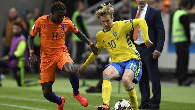 Le Néerlandais Quincy Promes (à gauche) au duel avec le Suédois Emil Forsberg (à droite) sous les yeux de l'entraîneur des Oranje, Danny Blind, lors du match nul entre les deux équipes (1-1) le 6 septembre dernier à Solna, dans la banlieue de Stockholm.  (PONTUS LUNDAHL / TT NYHETSBYR?N)