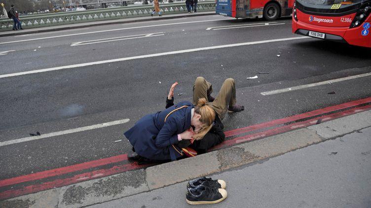 Une femme vient en aide à une personne blessée lors de l'attaque à Londres (Royaume-Uni), le 22 mars 2017. (TOBY MELVILLE / REUTERS)