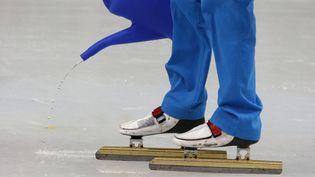 Un membre de l'organisation des JO verse de l'eau sur la piste du patinage de vitesse pour corriger les défauts de la glace, le 10 février 2014. (DAVID GRAY / REUTERS)