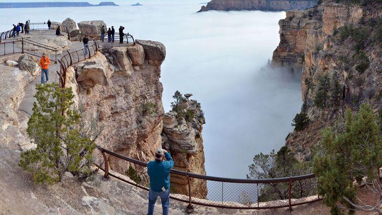 Des visiteurs contemplent le Grand Canyon (Arizona, Etats-Unis) rempli de nuages, un phénomène météorologique très rare, le 11 décembre 2014. (MICHAEL QUINN / AP / SIPA)