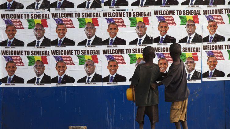 Des enfants regardent un mur recouvert des affiches représentant les présidents Barack Obama et Macky Sall, à Dakar (Sénégal), le 26 juin 2013. (JOE PENNEY / REUTERS)