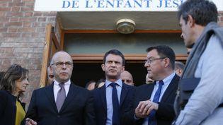 Le ministre de l'Intérieur Bernard Cazeneuve et le Premier ministre Manuel Valls à la sortie de l'église Sainte-Thérèse de Villejuif (Val-de-Marne), le 22 avril 2015. (KENZO TRIBOUILLARD / AFP)