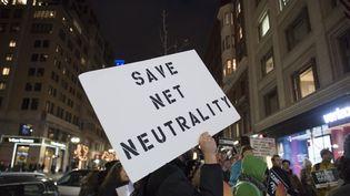 """Un manifestant avec une pancarte """"sauvez la neutralité du Net"""" à Boston, aux États-Unis, le 7 décembre 2017. (RYAN MCBRIDE / AFP)"""