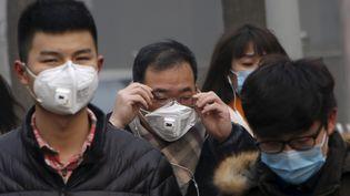 Des piétons portent un masque, lundi 30 novembre 2015 à Pékin (Chine). (KIM KYUNG HOON / REUTERS)