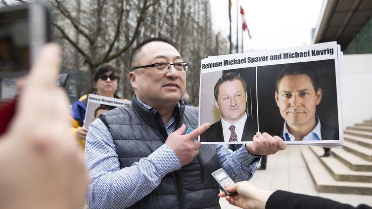 Le responsable d'une association pro-démocratie montre les portraits des Canadiens Michael Spavor et Michael Kovrig, lors d'un rassemblement de soutien à Vancouver en mars 2019. (JASON REDMOND / AFP)
