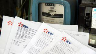 Des factures EDF devant un compteur électrique, janvier 2013. (JULIO PELAEZ / LE REPUBLICAIN LORRAIN / MAXPPP)