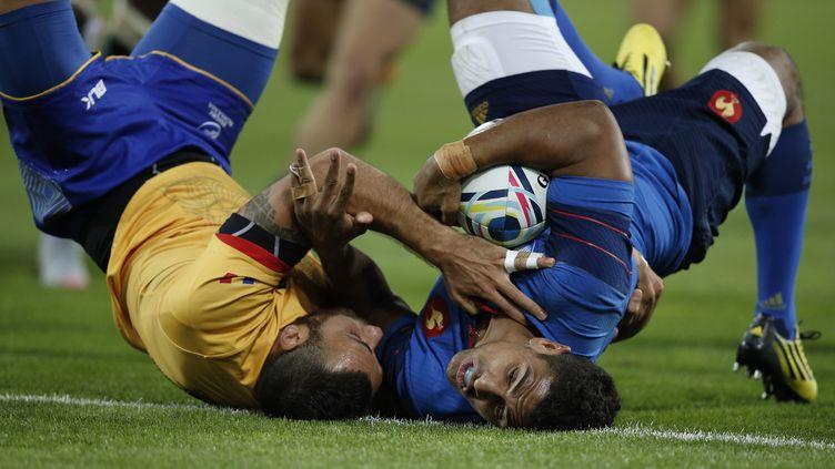 Wesley Fofana dans une position acrobatique face à un défenseur roumain (ADRIAN DENNIS / AFP)