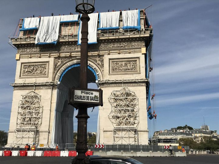 Le premier déroulé de tissu de l'empaquetage posthume de l'Arc de Triomphe par Christo, avec l'équipe de cordistes à droite du monument, dimanche 12 septembre 2021 à Paris. (VALERIE GAGET - FRANCE TELEVISIONS)