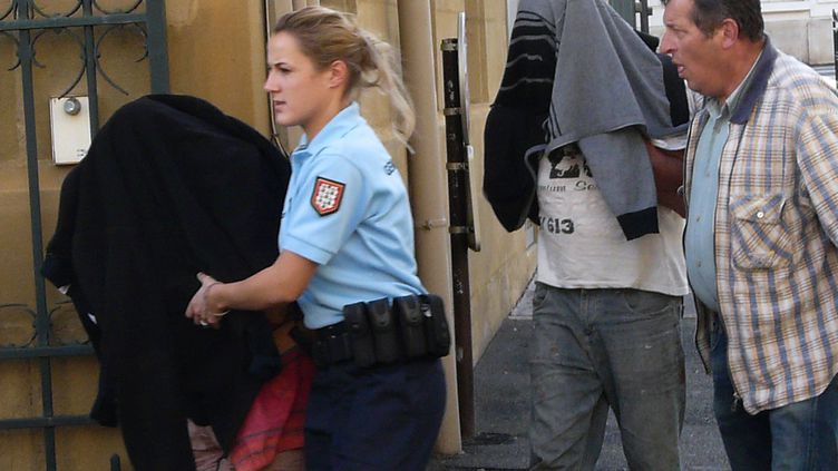 Masqués par des vêtements, les parents du bébé découvert dans un coffre arrivent au tribunal de Brive-la-Gaillarde (Corrèze), le 28 octobre 2013. (ERIC PORTE / AFP)