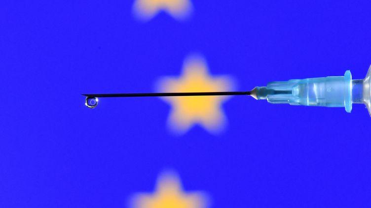 Illustration d'une seringue contenant un vaccin avec le drapeau de l'Union européenne en arrière plan. (JUSTIN TALLIS / AFP)