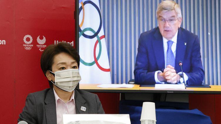 Seiko Hashimoto, la présidente de Tokyo 2020, et Thomas Bach (sur écran),le président du Comité international olympique (CIO), conversent lors d'une conférence de presse, le 21 juin 2021. (RODRIGO REYES MARIN / POOL)