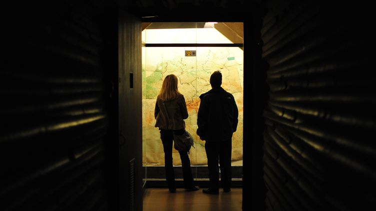 Des visiteurs scrutent une carte, au sein des War Rooms, dans la nuit du 4 octobre 2013, à Londres  (Carl Court / AFP)