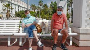 Deux hommes portent le masque, assis sur un banc de la Promenade des Anglais, à Nice (Alpes-Maritimes), le 31 mai 2020. (VALERY HACHE / AFP)