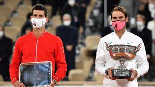 Le Serbe Novak Djokovic et l'Espagnol Rafael Nadal lors de la remise des prixaprès la finale de Roland-Garros, à Paris, le 11 octobre 2020.  (ANNE-CHRISTINE POUJOULAT / AFP)