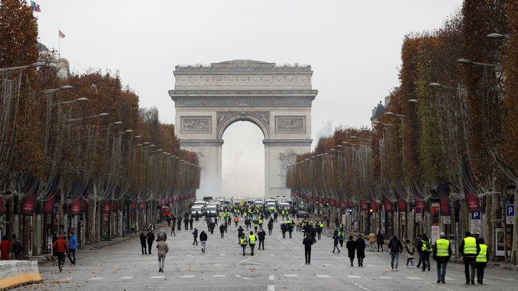 """Des """"gilets jaunes"""" commencent à investir dans le calme les Champs-Elysées, le 1er décembre 2018. (GEOFFROY VAN DER HASSELT / AFP)"""