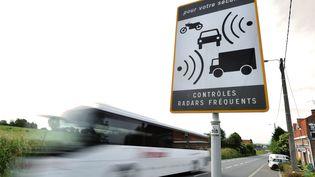 Un bus passe à coté d'un panneau signalant la présence d'un radar, le 24 Mai 2011 à Stazeele (Nord). (PHILIPPE HUGUEN / AFP)