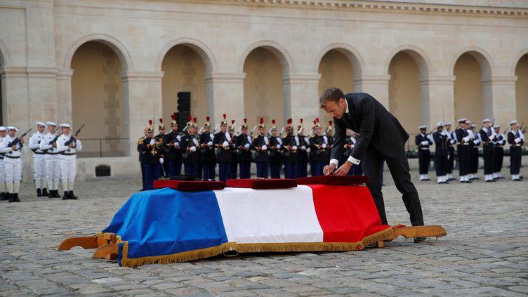 Le président de la République française, Emmanuel Macron, nomme le caporal-chef Maxime Blasco officier de la Légion d'honneur, lors d'une cérémonie nationale en hommage au soldat tué au Mali, le 29 septembre 2021 aux Invalides, à Paris. (STEPHANE MAHE / POOL / AFP)