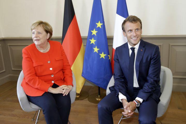 Le président français Emmanuel Macron porte la montre tricolore de Lip au poignet lors d'une rencontre avec la chancelière allemande Angela Merkel, à Marseille (Bouches-du-Rhône), le 7 septembre 2018. (CLAUDE PARIS / AFP)