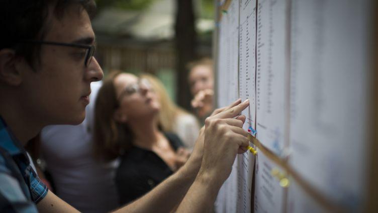 Un élève vérifie ses résultats au baccalauréat au lycée Georges-Brassens à Paris, le 7 juillet 2015. (MARTIN BUREAU / AFP)