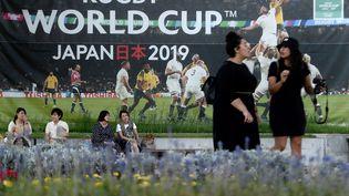 Des Japonaises discutent dans les rues de Kobe (Japon), le 17 septembre 2019, devant un affiche évoquant la Coupe du monde de rugby. (FILIPPO MONTEFORTE / AFP)