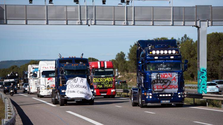 Des routiers défilent sous un portique écotaxe, le 9 novembre 2013, près de Martigues (Bouches-du-Rhône). (BERTRAND LANGLOIS / AFP)