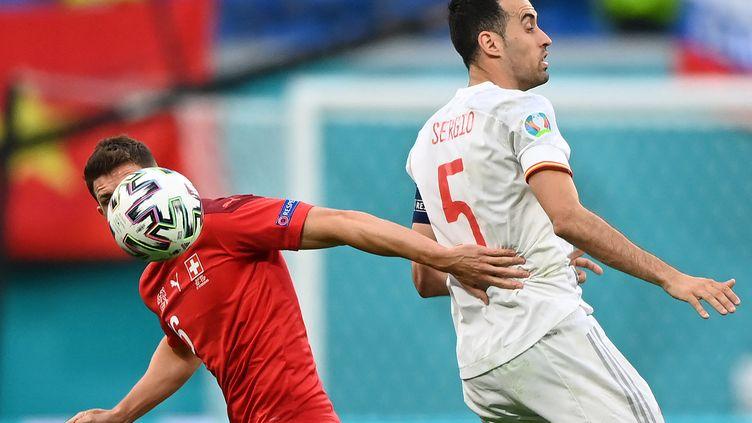 Le milieu de terrain suisseChristian Fassnacht au duel avec l'Espagnol Sergio Busquets, lors du quart de finale de l'Euro entre l'Espagne et la Suisse, le 2 juillet 2021. (KIRILL KUDRYAVTSEV / AFP)
