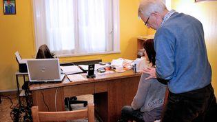 Un médecin ausculte une patiente àGodewaersvelde (Nord). (PHILIPPE HUGUEN / AFP)