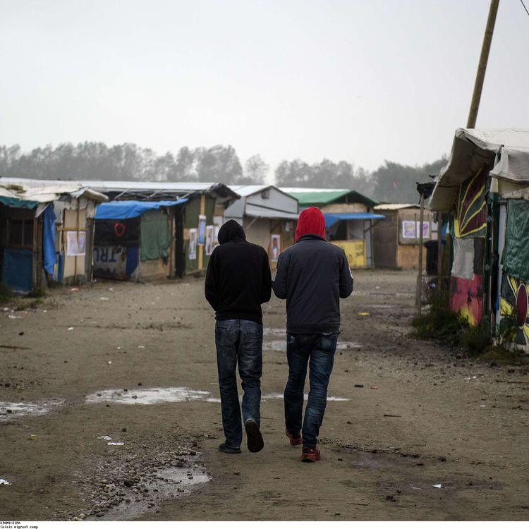 """Deux migrants marchent dans l'une des artères de la """"jungle"""" de Calais, le 23 octobre 2016. (SIPANY / SIPA)"""