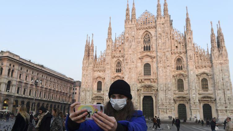 Une touriste sur la piazza del Duomo à Milan (Italie), le 24 février 2020. (MIGUEL MEDINA / AFP)