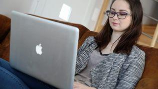 Une jeune femme utilisant un ordinateur Apple MacBook (illustration) (FRANCOIS DESTOC / MAXPPP)