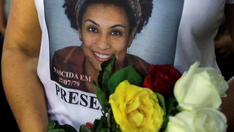 Une femme porte un tee-shirt en hommage à Marielle Franco lors d'une messe organisée à Rio de Janeiro un an après sa mort, le 14 mars 2019. (SERGIO MORAES / REUTERS)