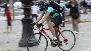 Un livreur à vélo dans une rue de Paris. (JACQUES DEMARTHON / AFP)