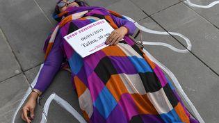 """France : une femme est étendue sur le sol avec une pancarte """"Stop féminicides"""" lors d'une manifestation pour la journée internationale pour les droits des femmes à Paris, le 8 mars 2019. (ALAIN JOCARD / AFP)"""