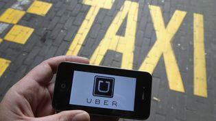 Un utilisateur ouvre l'application Uber sur son portable à Bruxelles (Belgique), le 13 septembre 2015. (NICOLAS MAETERLINCK / BELGA MAG / AFP)