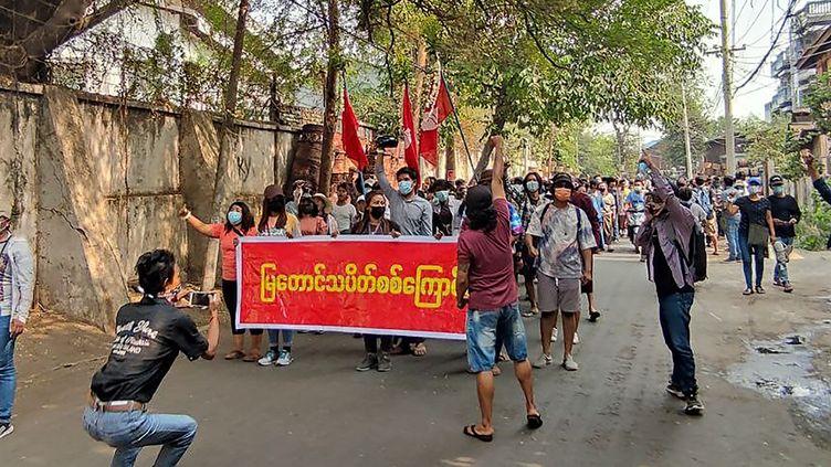 Cette photo prise et reçue d'une source anonyme via Facebook le 10 avril 2021, montre des manifestants tenant une banderole alors qu'ils défilent, lors d'une manifestation contre le coup d'État militaire à Mandalay. (HANDOUT / FACEBOOK / DOCUMENT ANONYME / AFP)