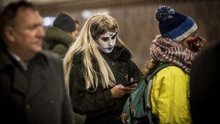 Une femme maquillée pour Halloween regarde son téléphone portable alors qu'elle attend le métro à Moscou, le 31 octobre 2018 (MLADEN ANTONOV / AFP)