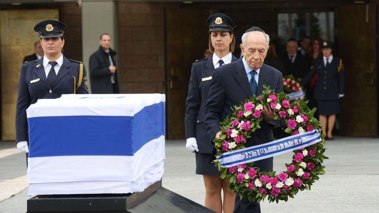 """Simon Peres dépose une couronne de fleurs devant le cercueil de son """"cher ami"""", qui""""ne connaissait pas la peur et n'a jamais craint de poursuivre un idéal."""" (URIEL SINAI / GETTY IMAGES)"""