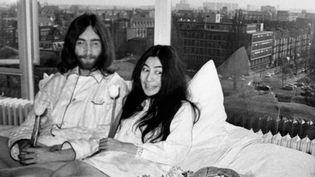 John Lennon et Yoko Ono reçoivent des journalistes dans leur chambre d'hôtel, le 25 mars 1969, à Amsterdam (Pays-bas). (ANP / AFP)