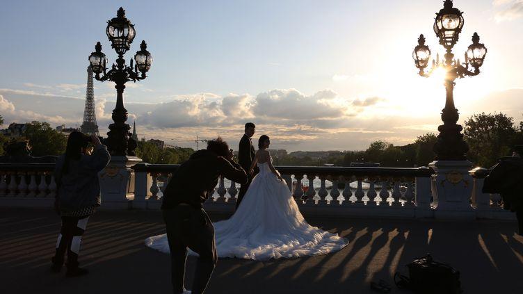 Des mariés qui see font prendre en photo à Paris, le 8 mai 2015. (LUDOVIC MARIN / AFP)