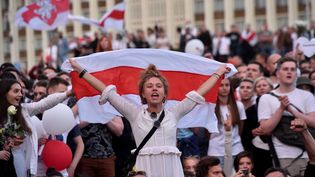 Une manifestante brandit l'ancien drapeau de la Biélorussie indépendante lors d'une manifestation contre le président Alexandre Loukachenko à Minsk, le 14 août 2020. (SERGEI GAPON / AFP)